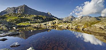 Reflection of the Cima Giner mountain in a mountain lake, Lago Nero, Brenta Adamello Nature Reserve, Trentino, Italy