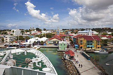 Bow of cruise ship MS Deutschland (Reederei Peter Deilmann) at a pier with colorful houses and shops near the port, St. John's, St. John, Antigua, Antigua and Barbuda, Caribbean
