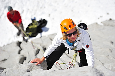Young woman climbing while young man belaying, Multerkarwand, Treffauer, Wegscheidalm, Wilder Kaiser, Kaiser Mountain Range, Tyrol, Austria