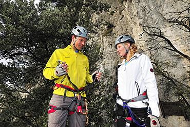 Young woman and young man preparing for fixed rope route Rino Pisetta, Lago die Toblino, Sarche, Calavino, Trentino, Trentino-Alto Adige, Suedtirol, Italy