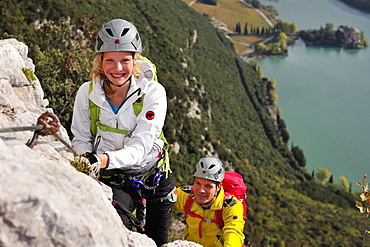 Young woman and young man climbing fixed rope route Rino Pisetta, Lago die Toblino, Sarche, Calavino, Trentino, Trentino-Alto Adige, Suedtirol, Italy
