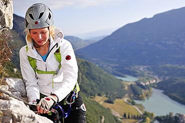 Young woman climbing fixed rope route Rino Pisetta, Lago die Toblino, Sarche, Calavino, Trentino, Trentino-Alto Adige, Suedtirol, Italy