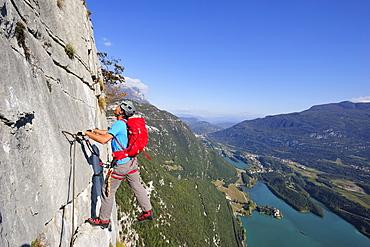 Young man climbing fixed rope route Rino Pisetta, Lago die Toblino, Sarche, Calavino, Trentino, Trentino-Alto Adige, Suedtirol, Italy