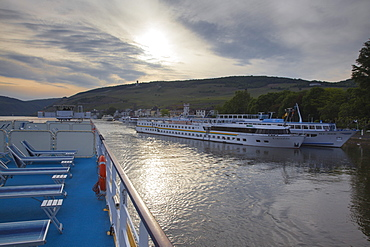 Deck of Rhine river cruise ship MS Bellevue and river cruise ships Exmeralda and Rex-Rhini alongside pier at dusk, Rudesheim am Rhein, Hesse, Germany, Europe
