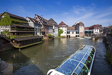 Restaurant Au Pont St. Martin and half-timbered houses and sightseeing boat on canal in La Petite France district, Strasbourg, Alsace, France, Europe