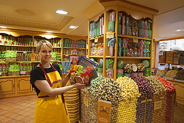 Salesgirl showing sweets for sale at La Cure Gourmande Biscuitier Sucrecuitier candy shop, Strasbourg, Alsace, France, Europe