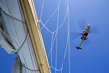 Man lowers himself from Swedish Sjoefartsverket rescue helicopter during rescue exercise on sailing cruise ship Star Flyer (Star Clippers Cruises), near Visby, Gotland, Sweden