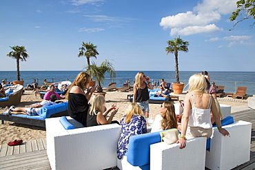 Young women relaxing on lounge chairs at the trendy Kallis Beach Club, Visby, Gotland, Sweden, Europe
