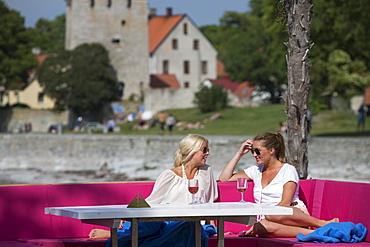 Two young women enjoying drinks and sunshine at the trendy Kallis Beach Club, Visby, Gotland, Sweden, Europe