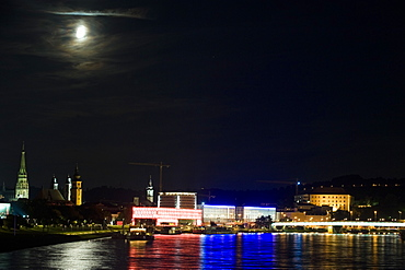 Full moon shining above the illuminated Museum of Modern Art on the Danube, Linz, Upper Austria, Austria