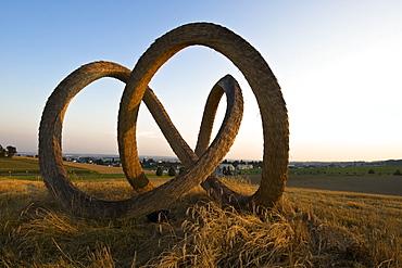 Sculpture made of straw on a field at dusk, Linz, Upper Austria, Austria
