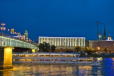 An excursion boat driving on the Danube at night, University of Art in the background, Linz, Upper Austria, Austria
