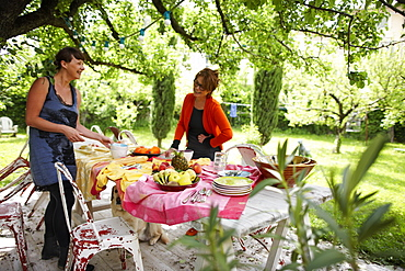 Women setting the breakfast table in the garden, B and B Chambre Avec Vue, Luberon, France