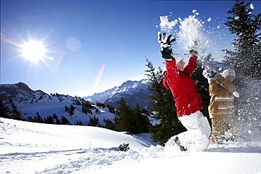 children throwing snow in the air, See, Tyrol, Austria