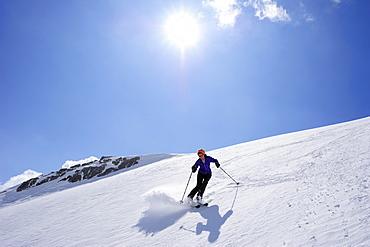 Woman backcountry skiing, descending on snow face, Schesaplana, Raetikon, Montafon, Vorarlberg, Austria