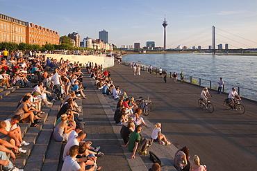 People sitting on the stairs to the Rhine river promenade, Duesseldorf, North Rhine-Westphalia, Germany, Europe