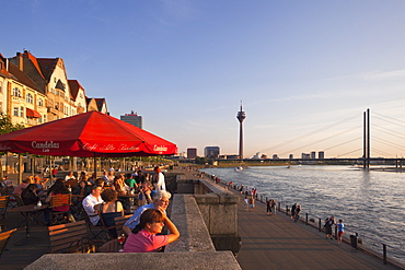 Terrace of a restaurant at the Rhine river promenade in the evening light, Duesseldorf, North Rhine-Westphalia, Germany, Europe