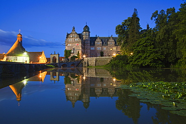 View over the pond onto Haemelschenburg castle in the evening, Emmerthal, Weser Hills, North Lower Saxony, Germany, Europe