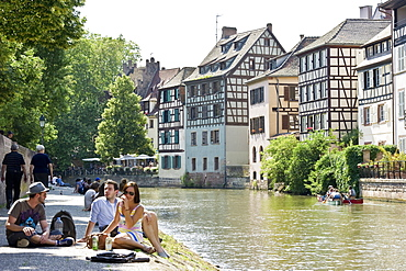 People sitting along the bank of the river, Petite France quarter, Strasbourg, Alsace, France