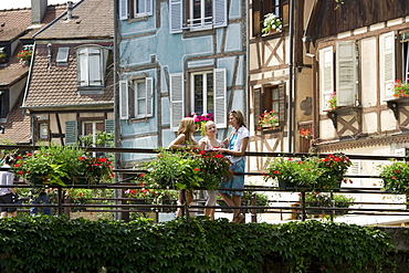 Mother and two daughters standing on a bridge in front of half-timbered houses in Petite Venise, Colmar, Alsace, France