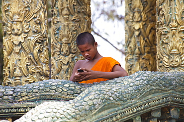 Young buddhistic monk with a mobile phone in a temple in the Kam, Cambodia, Asia