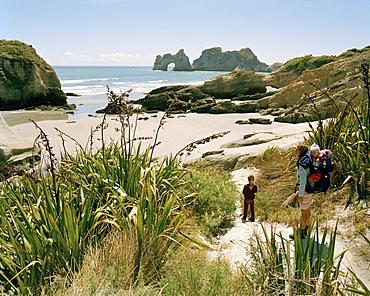 Mother with children hiking at Wharariki Beach, northwest coast, South Island, New Zealand