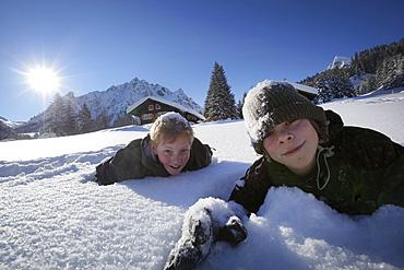 Two boys lying in snow, Gargellen, Montafon, Vorarlberg, Austria