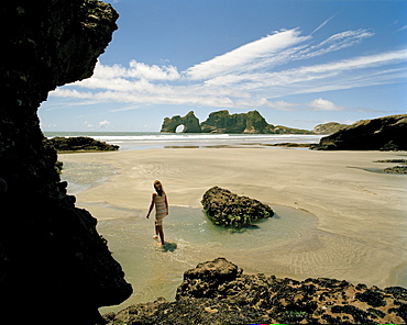 Woman walking through tidal pools at lowtide at Wharariki Beach, northwest coast, South Island, New Zealand