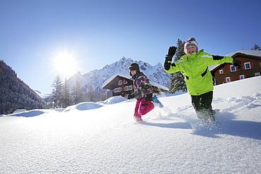 Two children running through snow, Gargellen, Montafon, Vorarlberg, Austria