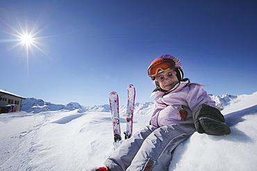 Girl (3 years) sitting in snow, Montafon, Silvretta, Sankt Gallenkirch, Vorarlberg, Austria