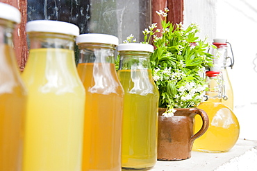 Woodruff syrup, juice and liqueur on a window sill, homemade