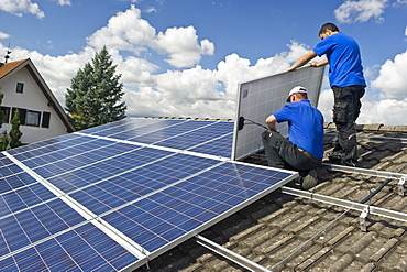 Two persons installing a solar plant, Freiburg im Breisgau, Black Forest, Baden-Wuerttemberg, Germany, Europe