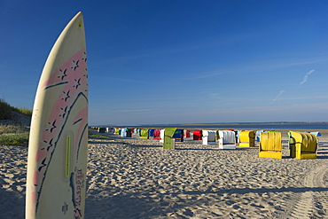 Colourful beachchairs and surfboard on the beach, Utersum, Foehr, North Frisian Islands, Schleswig-Holstein, Germany, Europe