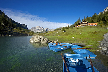 Rowing boats and guesthouse at lake Oeschinensee, Kandersteg, Bernese Oberland, Canton of Bern, Switzerland, Europe