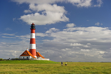 Westerheversand lighthouse and cyclists, Westerhever, Wadden Sea National Park, Eiderstedt peninsula, North Frisian Islands, Schleswig-Holstein, Germany, Europe