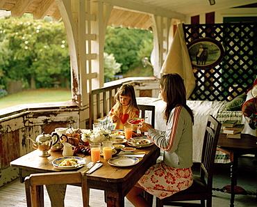 A woman and a girl having breakfast on the balcony, Rowendale Homestead, Okains Bay, Banks Peninsula, South Island, New Zealand