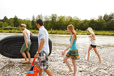 Young people with a rubber dinghy on the Isar riverbank, Munich, Bavaria, Germany