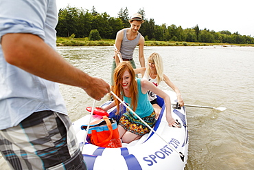 Young people, with a rubber dinghy at the Isar river, Munich, Bavaria, Germany