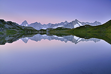 Mont Blanc range with Grandes Jorasses and Mont Dolent reflecting in a mountain lake, Pennine Alps, Aosta valley, Italy