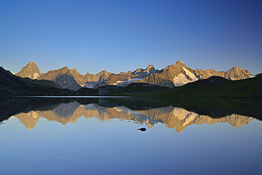 Mont Blanc range with Grandes Jorasses and Mont Dolent reflecting in mountain lake, Pennine Alps, Aosta valley, Italy