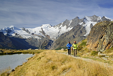 Woman and man hiking near a mountain lake with view to Mischabel range with Allalinhorn, Alphubel, Taeschhorn, Dom and Lenzspitze, Pennine Alps, Valais, Switzerland