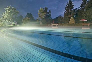 Fog at water surface at open air swimming pool Spiesel, Aalen, Ostalbkreis, Swabian Alb, Baden-Wuerttemberg, Germany