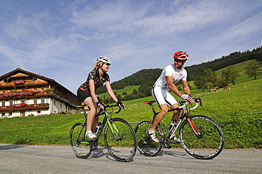 Couple on a racing bike, Kelchsau, Kitzbuehel Alps, Tyrol, Austria