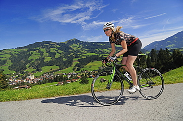 Woman on a racing bike, Schwaigerberg, Hopfgarten, Hohe Salve, Kitzbuehel Alps, Tyrol, Austria