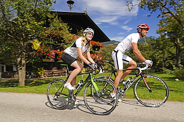 Couple on racing bikes, Schwaigerberg, Hopfgarten, Hohe Salve, Kitzbuehel Alps, Tyrol, Austria