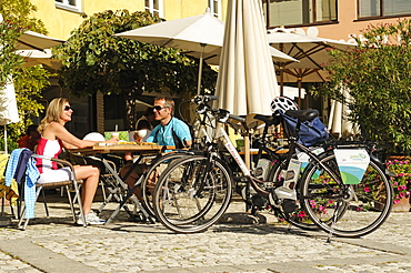 Couple having a break with apple strudel and cappucino, electric bikes, E-bikes, South Tyrol, Italy