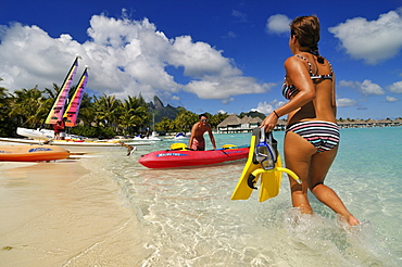 Couple with boat about to go snorkelling, Saint Regis Bora Bora Resort, Bora Bora, Society Islands, French Polynesia, Windward Islands, South Pacific