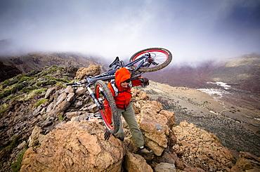 Man carrying mountain bike over a ridge, Tenerife