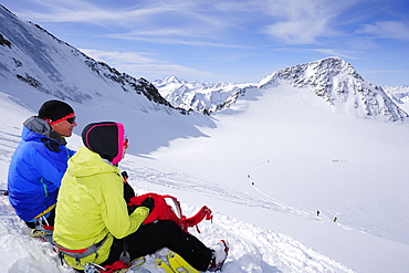 Two backcountry skiers resting during ascent to Wildspitze, Oetztal Alps, Tyrol, Austria