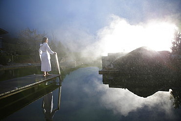 Woman on a jetty at a natural source pond, Tannheim, Tannheim Valley, Tyrol, Austria